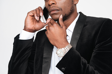 Cropped photo of handsome african businessman talking by his phone. Isolated over white background.