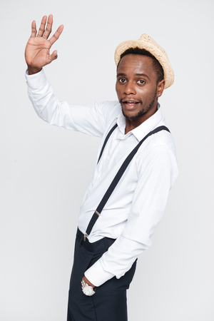 Image of handsome african man wearing hat posing in studio and waving. Isolated over white background. Look at camera. Stock Photo