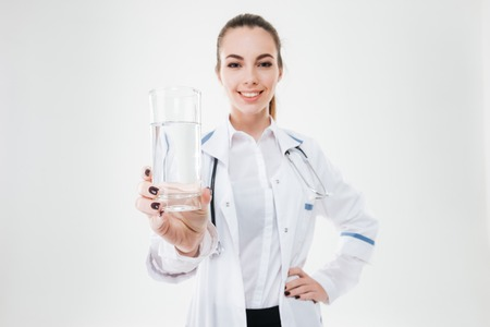 doctor giving glass: Happy attractive young woman doctor standing and giving young glass of water over white background Stock Photo