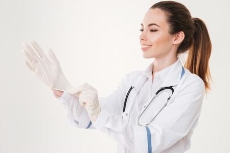 Cheerful attractive young woman doctor puttin on rubber gloves over white background Stock Photo