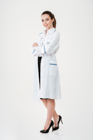 Full length of happy confident young woman doctor standing with arms crossed over white background