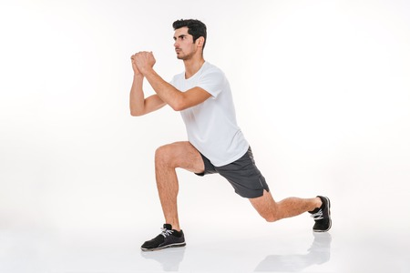 Full length portrait of a fitness man doing squats exercises isolated on a white background
