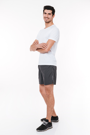 Full length portrait of a smiling sports man standing with arms folded isolated on a white background Stock Photo