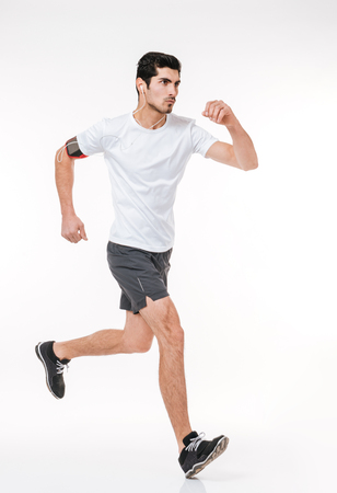 Portret van de zijaanzicht het volledige lengte van een geconcentreerde jonge sportenmens die met oortelefoons lopen die op een witte achtergrond worden geïsoleerd