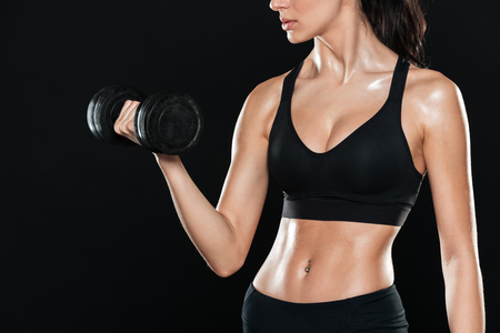 Cropped photo of fitness lady in gym standing over black background and make sport exercises with dumbbell.