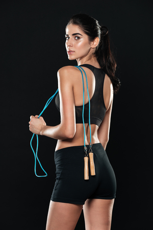 Back view of fitness woman in gym standing over black background and make sport exercises holding jumping rope. Stock Photo