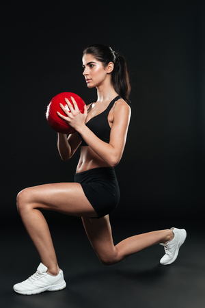 Full length of a concentrated sports woman doing squats and holding weight ball over black background