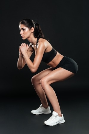 Side view of a young fit young woman doing squats over black background Stock Photo