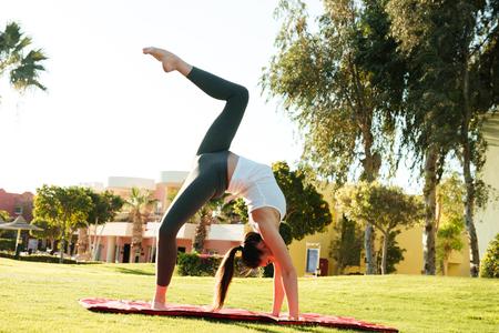 Barefoot jonge sportvrouw strekt en oefeningen op yoga mat buitenshuis Stockfoto