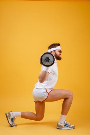 koncentrovaný: Boční pohled na retro fitness muž dělá dřepy s činkou izolovaných na oranžovém pozadí