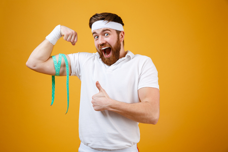Portrait of a happy excited fitness man measuring his biceps and showing thumbs up gesture isolated on a orange background Stock Photo