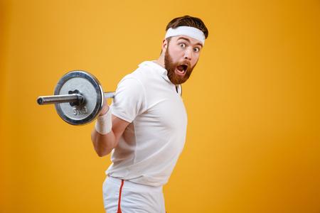 levantar peso: Retrato de un excitado barbudo fitness hombre ejercicio con barbell aislado en un fondo blanco Foto de archivo