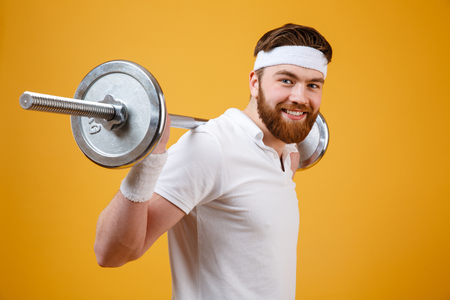 Portrait of a smiling cheerful sports man doing exercises with barbell and looking at camera ver yellow background