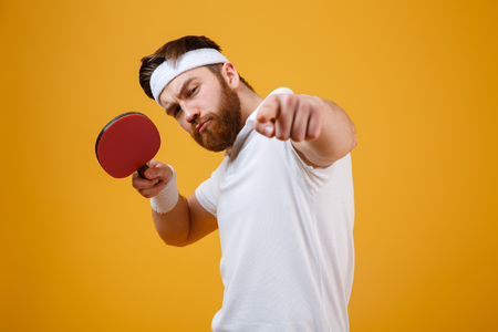Photo of handsome serious young sportsman dressed in white t-shirt standing isolated over yellow background holding racket for table tennis. Looking at camera while pointing.