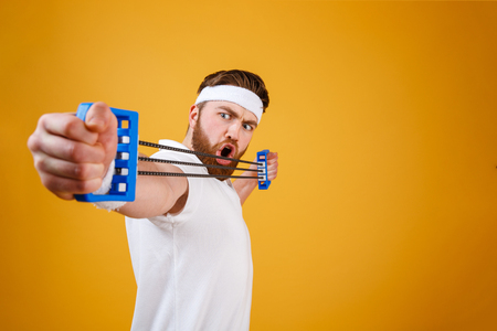 Young athletic man exercising with chest expander or resistance band over orange background