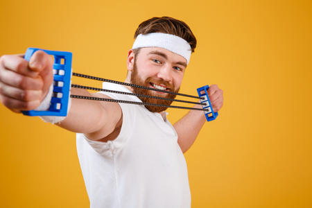 Close up portrait of a young athletic man exercising and doing fitness with a chest expander over orange background Stock Photo