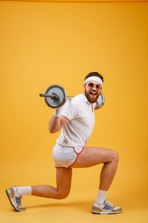 concentrate on: Side view of an excited retro fitness man doing squats with barbell and looking at camera isolated on a orange background