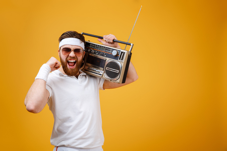 Image of screaming young man wearing sunglasses holding tape recorder dressed in white t-shirt isolated over yellow background. Looking at camera make winner gesture. Stock Photo