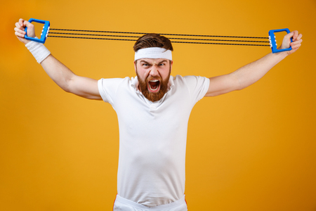 Image of screaming young sportsman make sport exercises with sport ecquipment dressed in white t-shirt standing isolated over yellow background. Looking at camera. Stock Photo