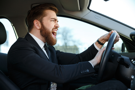 trafic: Side view of angry business man in suit driving a car and beeps Stock Photo