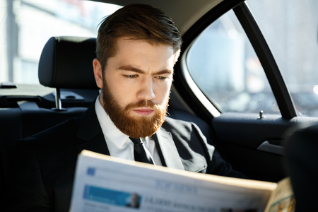 Concentrated bearded business man reading newspaper while sitting in car. Stock Photo