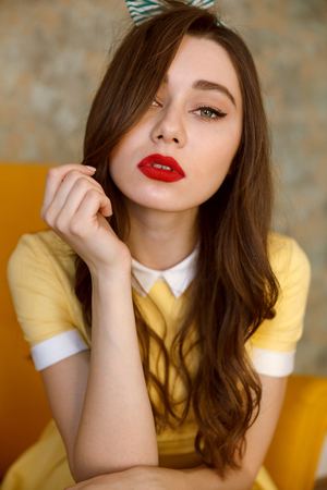 Close up portrait of a sensual beautiful pin up girl in yellow dress sitting in chair and looking at camera Imagens