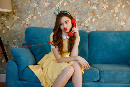Image of bored young pin-up lady with red lipstick sitting on sofa at home. Looking at camera while talking by phone.