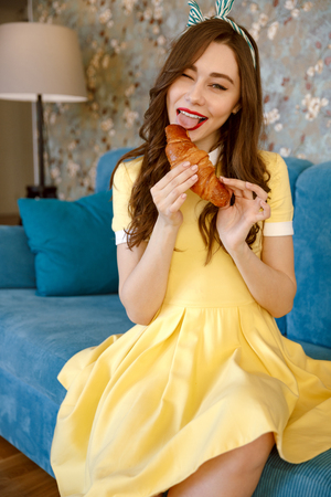 Picture of smiling young pin-up lady with red lipstick sitting on sofa at home. Looking at camera and eating croissant. Stock Photo
