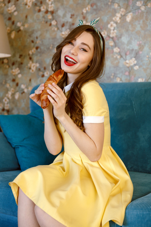Photo of happy young pin-up lady with red lipstick sitting on sofa at home. Looking at camera and eating croissant. Stock Photo