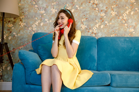 Photo of happy young pin-up lady with red lipstick sitting on sofa at home. Looking aside while talking by phone.