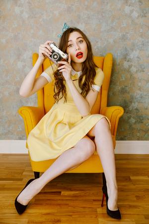 Portret van een mooie jonge pin-up vrouw in jurk zittend in een stoel en het nemen van foto met retro camera binnenshuis