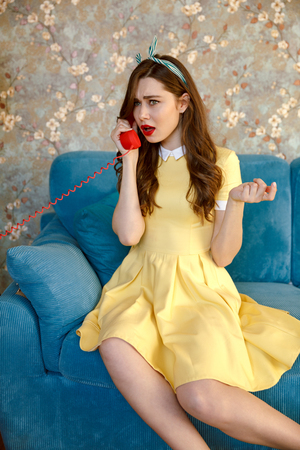 Picture of serious young pin-up lady with red lipstick sitting on sofa at home. Looking aside while talking by phone.