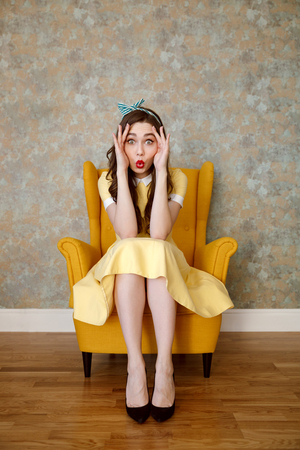 Vertical image of funny woman in yellow dress which sitting on armchair and holding hands near the eyes while looking at camera Stock Photo