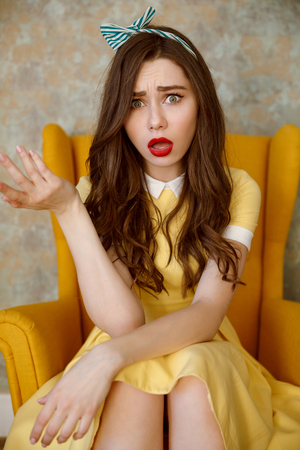 Vertical image of Uncomprehending woman in yellow dress which sitting on armchair and looking at camera. Stock Photo