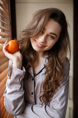 Vertical image of happy woman in shirt which holding tangerine and looking at camera while standing near the window Фото со стока