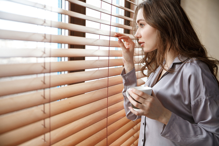 Side view of woman in shirt which looking at window and holding cup of coffee Stock Photo