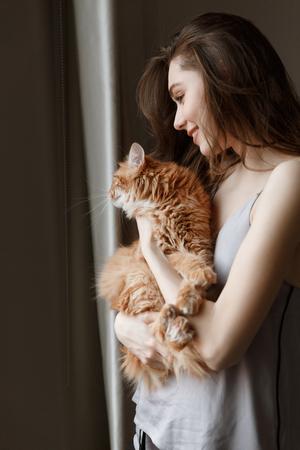 Vertical image of pleased woman in nightie which holding cat in hands Banco de Imagens