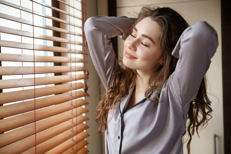 Pleased woman in shirt which standing near the window with closed eyes