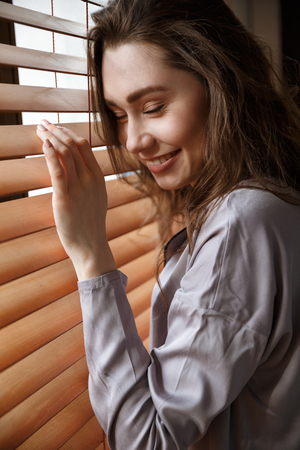 Vertical image of pleased woman in shirt which standing near the window