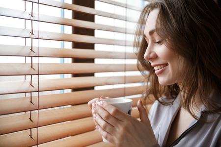 Cropped image of woman in shirt which standing near the window and holding cup of coffee in hands