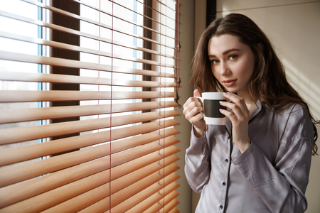 Young woman in shirt which standing near the window and holding cup of coffee while looking at camera