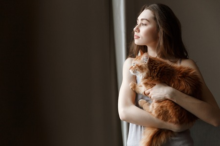 Young woman in nightie which holding cat in hands while looking away