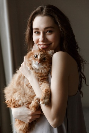 Vertical image of smiling woman in nightie which standing with cat in hands while looking at camera