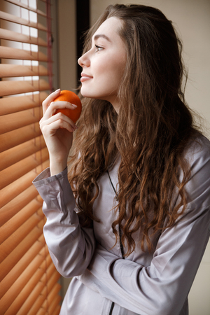 Vertical image of pleased woman in shirt which holding tangerine while looking at window