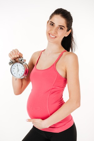 Smiling lovely pregnant woman holding alarm clock isolated on white background