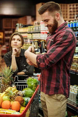 nespokojen: Picture of young loving couple in supermarket with shopping trolley choosing products. Dissatisfied woman looking at man holding beer.