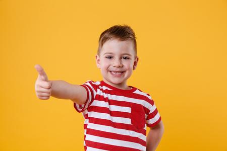오렌지 배경 위에 절연 엄지 손가락을 보여주는 웃는 어린 소년의 초상화 스톡 콘텐츠