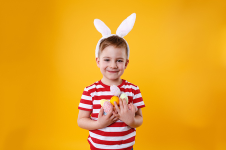 Portrait of a smiling adorable little boy wearing bunny ears and holding bunch of colorful easter eggs isolated over orange background