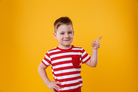 looking away from camera: Smiling happy boy pointing finger away at copyspace isolated over orange background Stock Photo