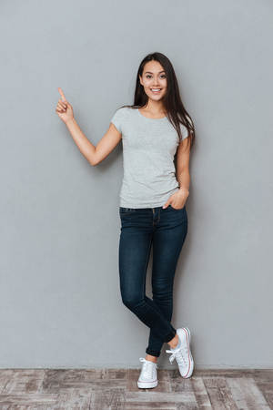 Vertical image of smiling woman ponting away and looking at camera while holding arm in pocket and posing in studio over gray background Фото со стока